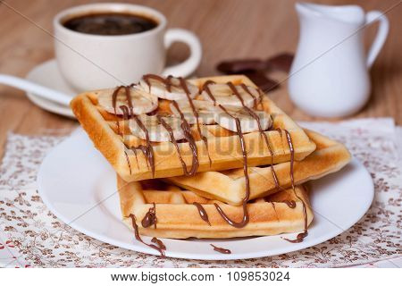 Breakfast  waffles with bananas, chocolate syrup and coffee
