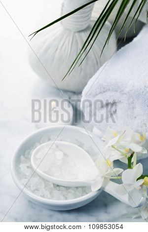 Spa background (white orchid, herbal compress stamps, sea salt, towel and massage stones)