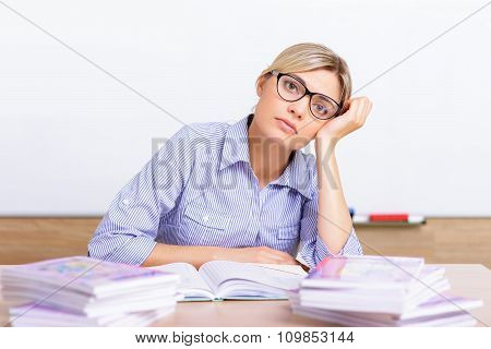 Young teacher surrounded with assignments.