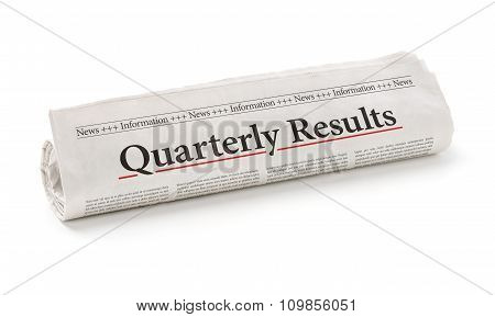 Rolled Newspaper With The Headline Quarterly Results
