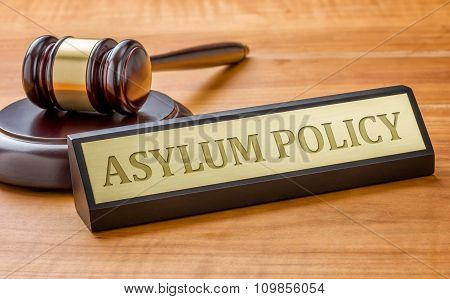 A Gavel And A Name Plate With The Engraving Asylum Policy