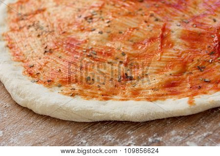 Cooking of the pizza dough, covered with sauce and seasonings