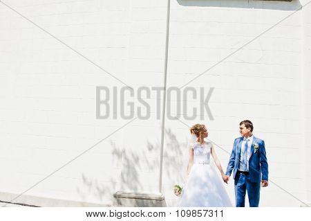 Wedding Couple Near White Stone Wall With Columns