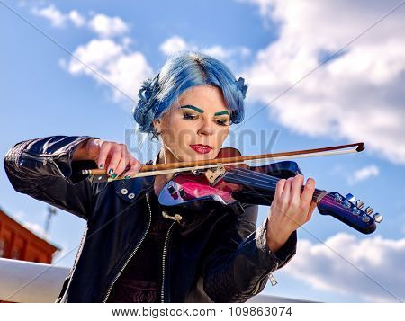 Music street performers girl violinist with blue hair and eyebrow playing  aganist sky with clouds outdoor.