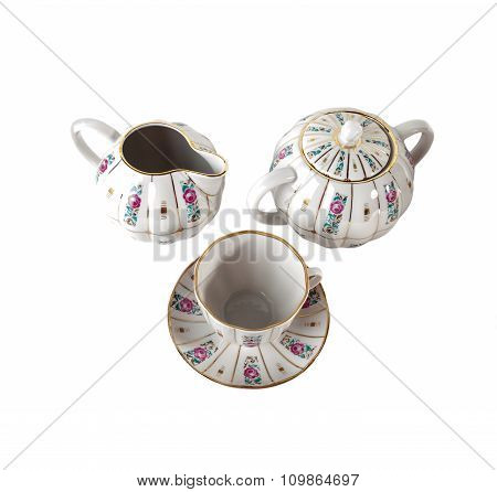 Porcelain Gravy Boat, sugar bowl, teacup and saucer with ornament of roses in retro style isolated