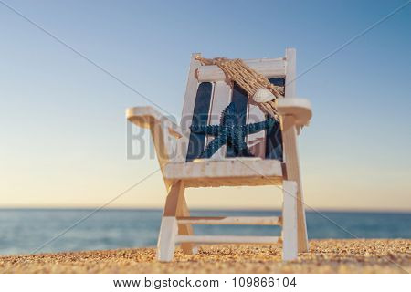 tropical beach with a sun-lounger facing the blue sea at dawn