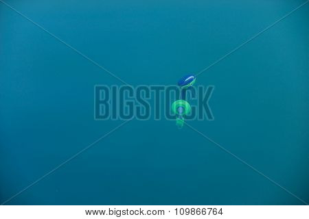 Headphones under water isolated on blue background.