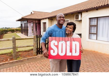 happy african couple standing outside their house and holding sold sign