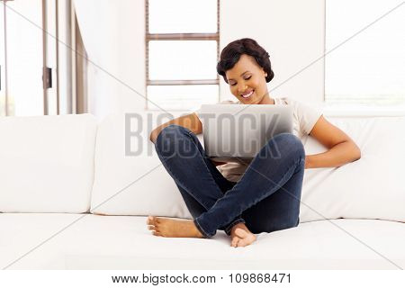 attractive african girl using laptop computer at home