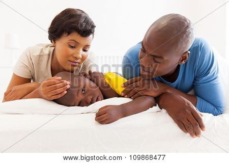 portrait of caring african parents and sick son lying on the bed
