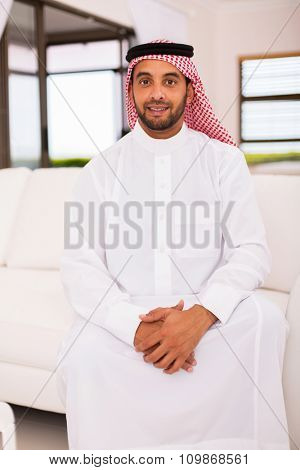 handsome middle eastern man sitting on the couch at home