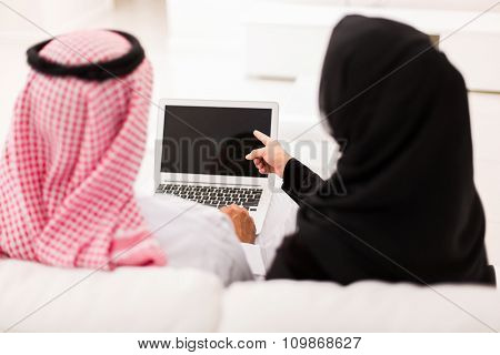 back view of muslim couple pointing at laptop screen