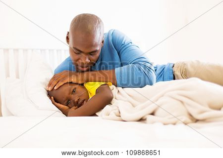 loving african father taking care of his ill son on bed