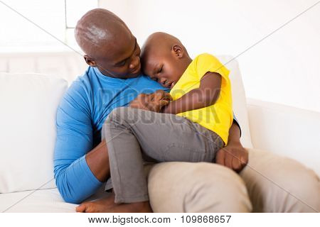 african american father comforting his ill son at home