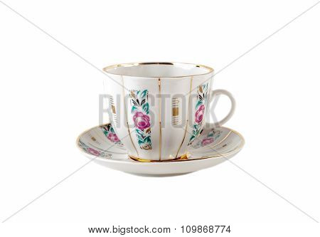 Porcelain teacup and saucer with floral roses ornament in retro isolated over white