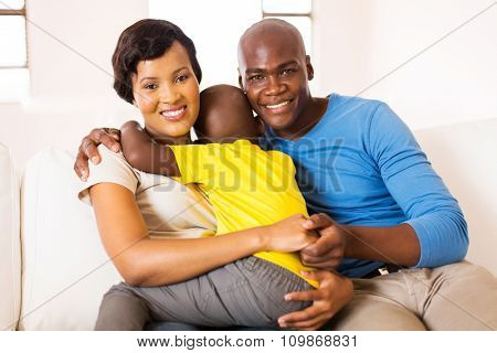 lovely young african family of three sitting at home