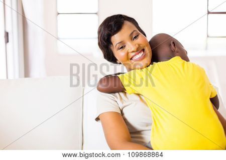 beautiful young african woman with her son relaxing at home