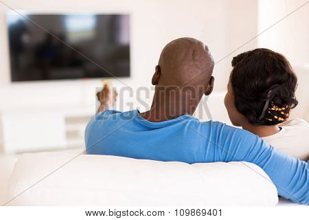 back view of young african couple watching tv in the living room at home