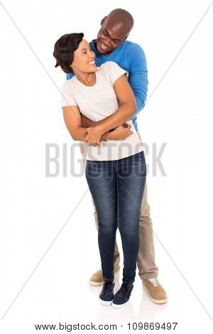 happy african man embracing his beautiful girlfriend from behind