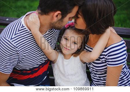 Portrait Of Happy Parents With Child In Summer.