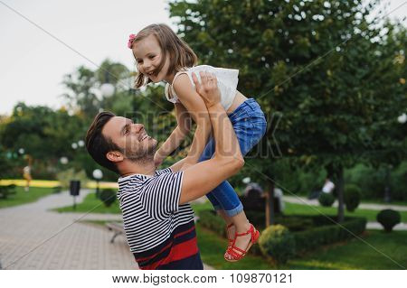 Happy Family Dad Throws Child Daughter Up On A Walk  In Park