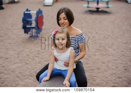 Beautiful , Cheerful Mother And Daughter On Swing