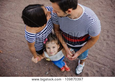Parents With Child Stand Having Joined Hands