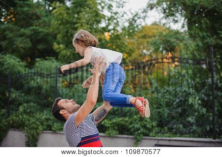 Father Having Fun And Throwing Up His Daughter In Park