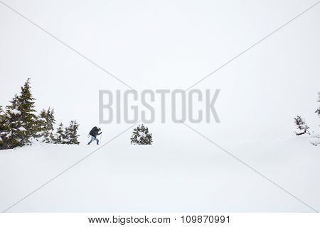 Male mountain climber with huge backpack and trekking poles having hard winter hiking trip after blizzard in Austrian Alps