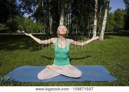 blonde real girl doing yoga in green park, gymnastic head over hills