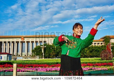 Beijing , China - September 24, 2014: Chinese woman in traditional costume dancing in Tiananmen Square Beijing China
