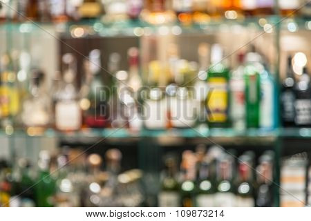 Glass bar counter with blurred shelves with alcohol bottles on the background.