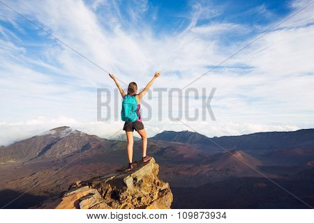 Young happy woman hiker with backpack standing on mountain peak with open arms