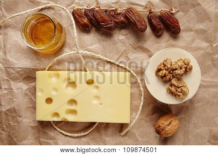 Emmental Cheese With Dried Datils, Walnut, Honey On Craft Brown Paper And Rope
