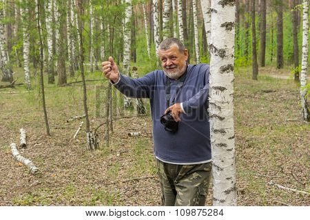 Elderly man with camera standing near birch