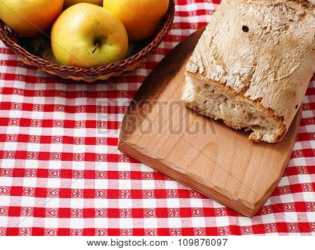 Picnic stil life with bread on wooden cutting board and apples in a basket on red checkered table cloth