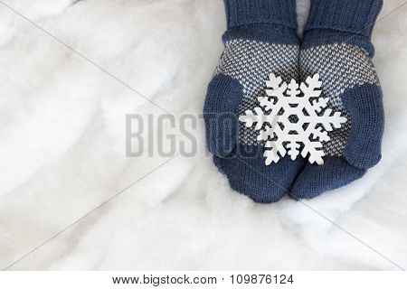 Woman Hands In Light Teal Knitted Mittens Are Holding Snowflake On Snow Background.