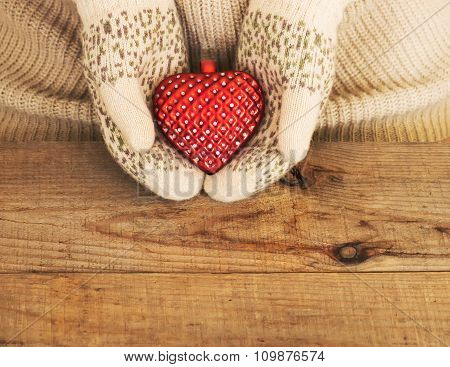 Woman Hands In Light Teal Knitted Mittens Are Holding Red Heart On Wooden Background.