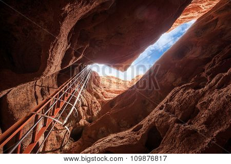 top of cave with iron ladder in red sandstone