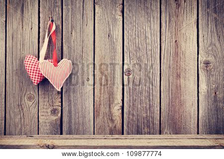 Two Valentines day hearts on rustic wooden wall with copy space. Toned