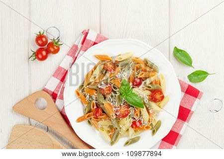 Colorful penne pasta with tomatoes and basil on wooden table. Top view