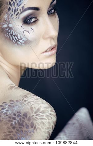 fashion portrait of pretty young woman  creative make up like a snake, fashion victim with python sk