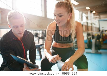 Personal Trainer Helping Young Woman With Her Fitness Plan