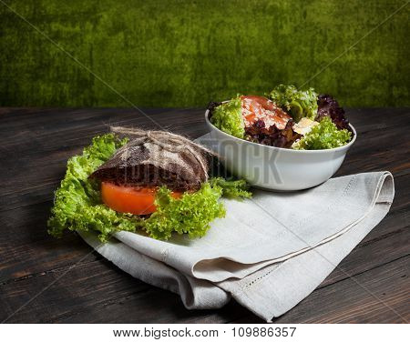 Grain bread sandwiches and fresh vegetables on wood