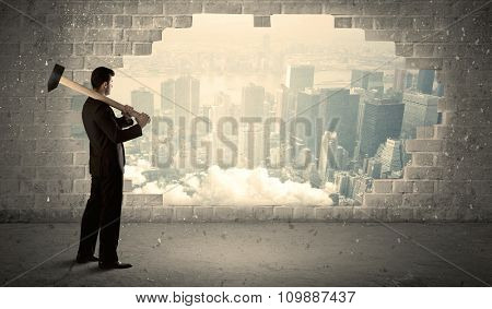 Business man hitting wall with hammer on city view background