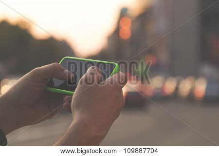 Using cellphone outdoors - with defocused city lights in the background.
