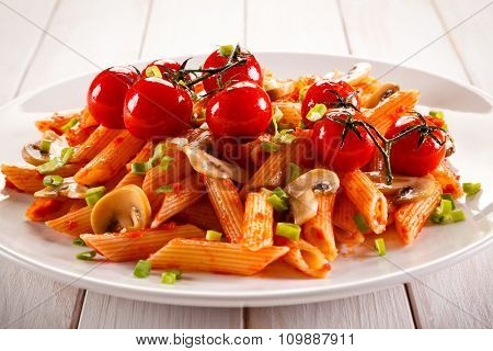Penne pasta with meat, tomato sauce and vegetables