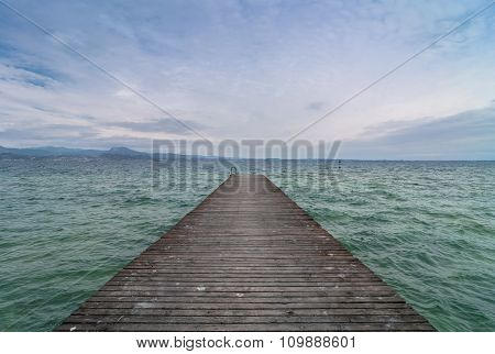 Wooden Pier And Cloudy Sky Over Garda Lake - Italy