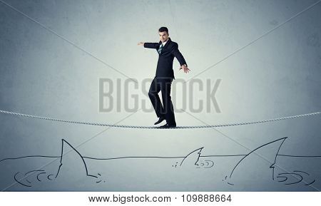 A brave businessman walking on tightrope expanded aboved rawn ocean with shark fin concept