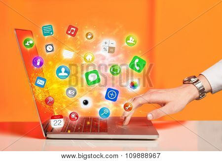 Hand pressing modern laptop with mobile app icons and symbols comming out
